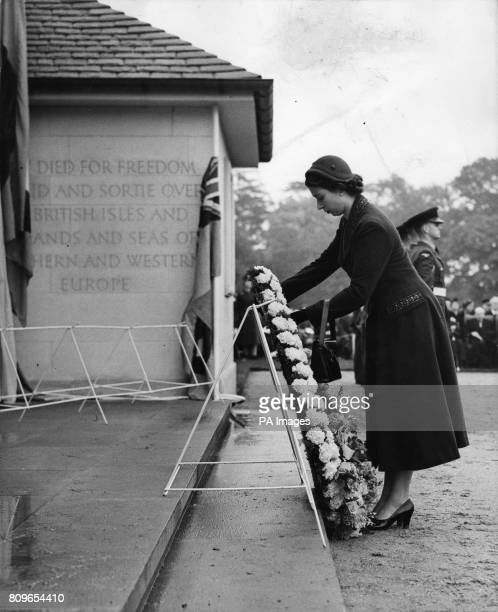 Queen Elizabeth II lays a wreath of pale pink carnations orchids and lilyofthevalley on the first step leading to the central arch of the Runnymede...