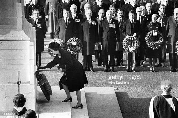 Queen Elizabeth II lays a wreath of poppies at the Cenotaph watched by the Prime Minister and members of the Government on the 60th anniversary of...