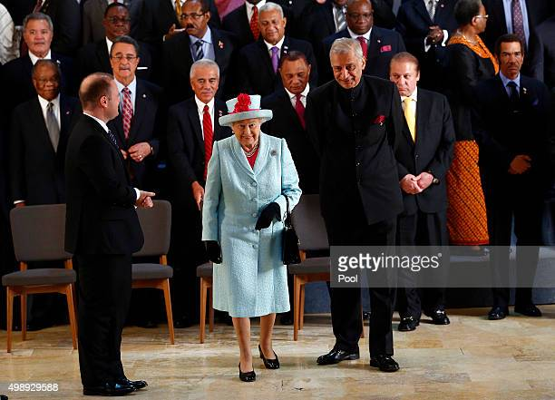 Queen Elizabeth II leaves with Commonwealth Secretary General Kamalesh Sharma following the family photograph at the CHOGM opening ceremony at the...
