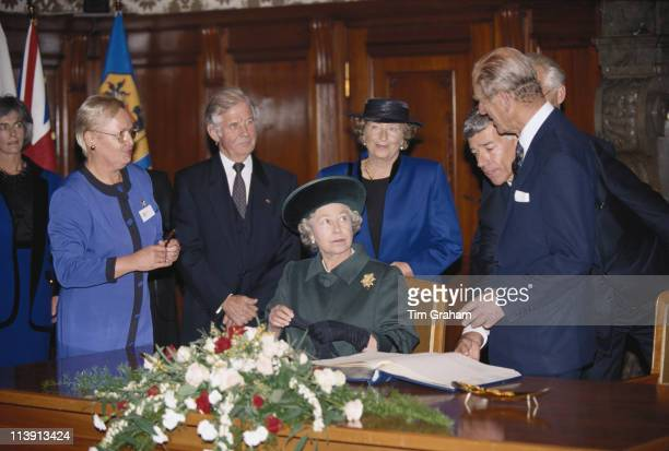 Queen Elizabeth II looking up at Prince Philip after signing the guest book at the Kreuzkirche in Dresden Germany 22 October 1992