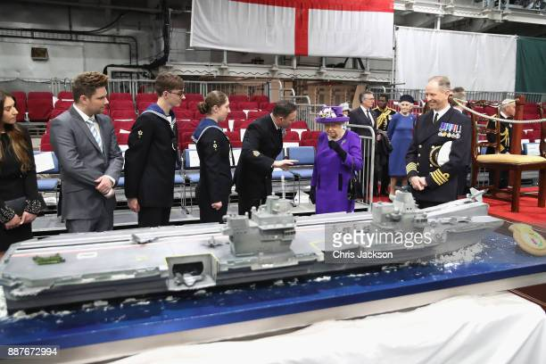 Queen Elizabeth II looks at a cake made by David Duncan during the Commissioning Ceremony of HMS Queen Elizabeth at HM Naval Base on December 7 2017...