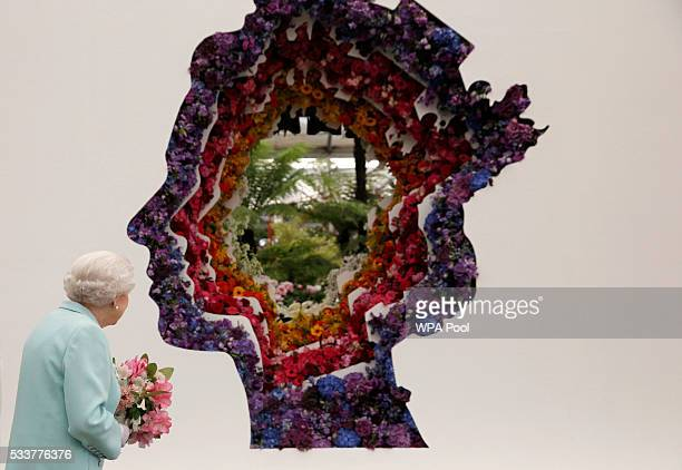 Queen Elizabeth II looks at a floral exhibit by the New Covent Garden Flower Market which features an image of the Queen at Chelsea Flower Show press...