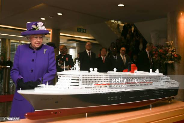 Queen Elizabeth II looks at a model of the RMS Queen Mary 2 transatlantic ocean liner during a visit to the International Maritime Organization to...
