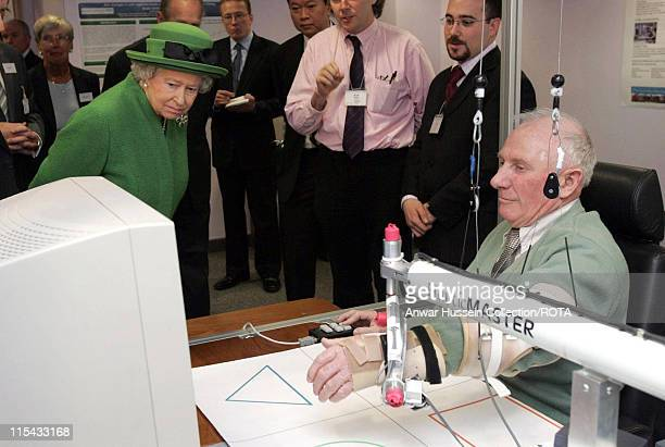 Queen Elizabeth II looks at a monitor as stroke patient John Dobson demonstrats a Robotic Arm in the cybernetics departmentat The Royal Berkshire...