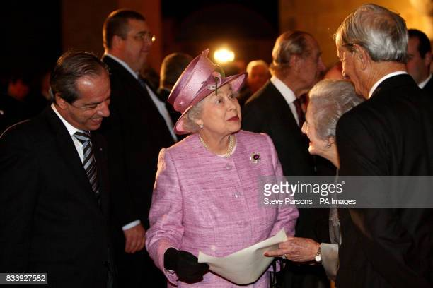 Queen Elizabeth II looks at a photo while she meets fellow Diamond Wedding Anniversary couples during her visit at the the Upper Barrakka Gardens in...