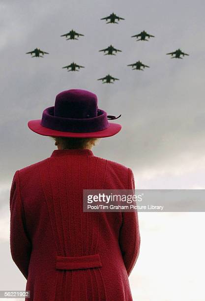 Queen Elizabeth II looks at a plane fly-by during a visit to RAF Coltishall watches RAF Jaguar planes in a diamond 9 formation on November 17, 2005...