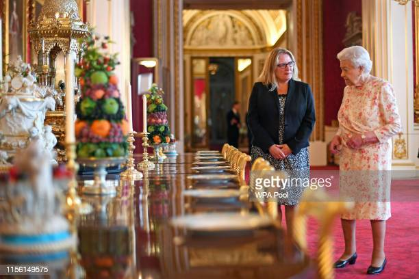 Queen Elizabeth II looks at a recreation of the 'Victoria' pattern dessert service in the State Dining Room as part of the exhibition to mark the...