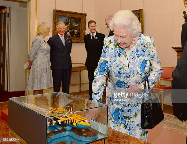 Queen Elizabeth II looks at a replica canoe of the one she and the Duke of Edinburgh arrived by during their visit to Tuvalu in 1982, which was...
