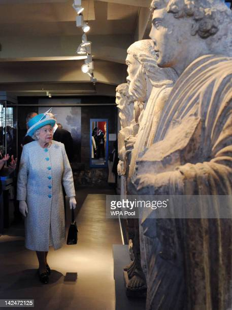 Queen Elizabeth II looks at a row of stone statues during a visit to the Yorkshire Museum after the Royal Maundy Service held in York Minster on...