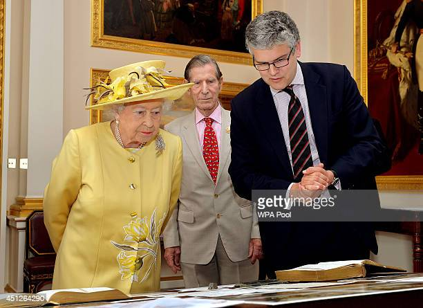 Queen Elizabeth II looks at an exhibition of World War One memorabilia inside Buckingham Palace before attending the 'Not Forgotten' Association...