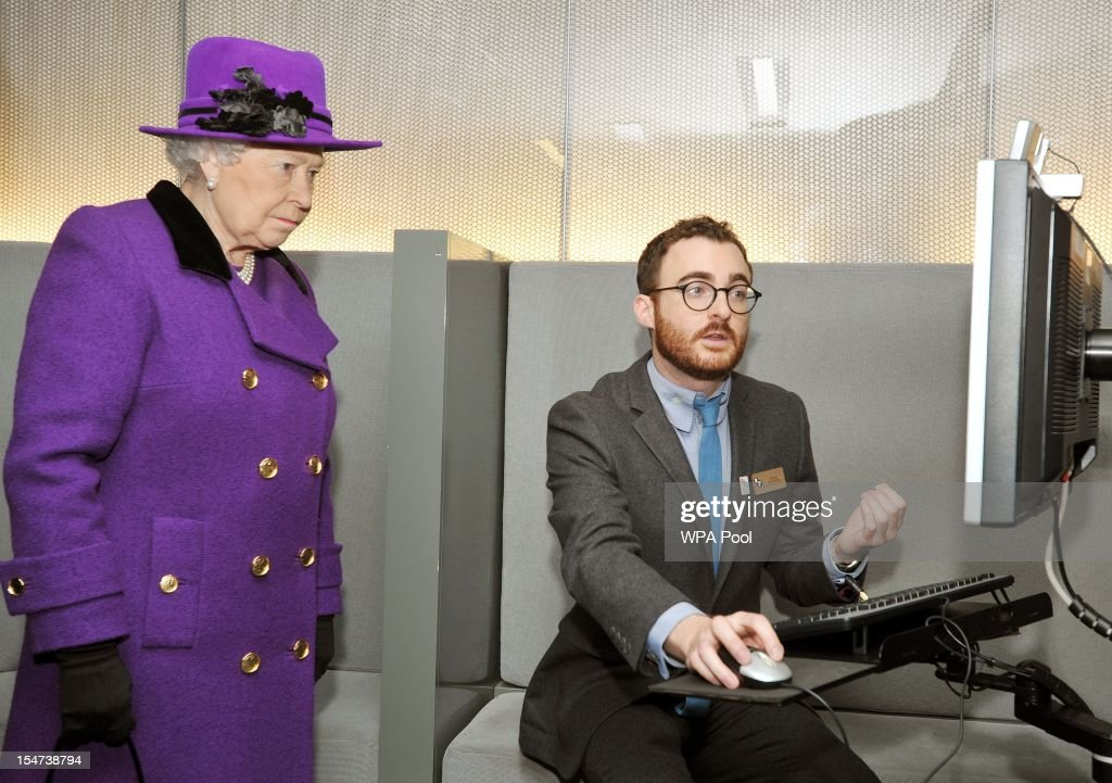 Queen Elizabeth II looks at an old restored film on a computer screen during a visit to the British Film Institute on October 25, 2012 on the Southbank in London, England.