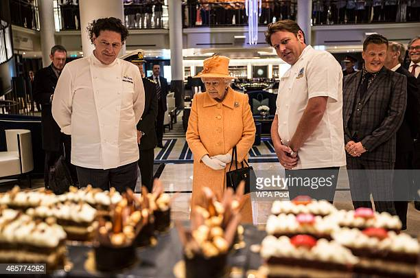 Queen Elizabeth II looks at cakes and sweets on the patisserie counter on board the new PO cruise liner 'Britannia' with chefs Marco Pierre White and...