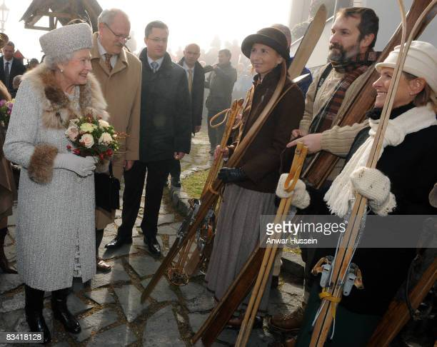 Queen Elizabeth II looks at locals holding antique skis as she tours Hrebienok Ski Resort on the second day of a tour of Slovakia on October 24, 2008...