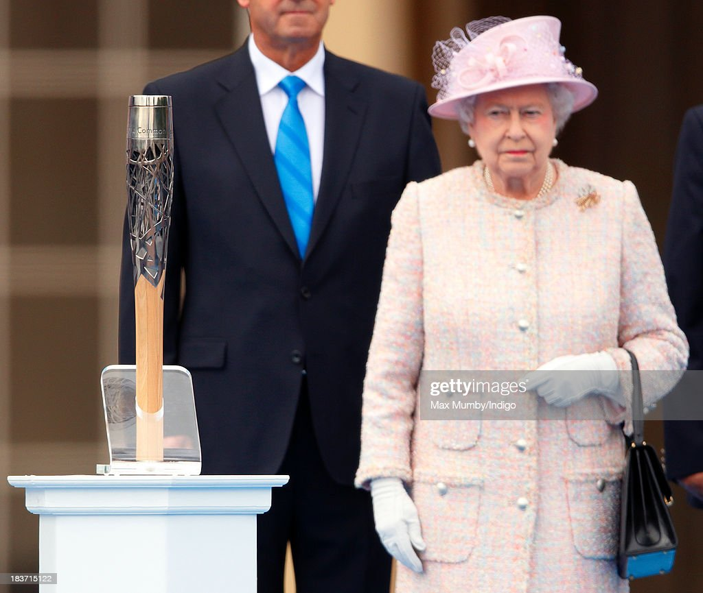 Queen Elizabeth II looks at the Commonwealth Games Baton during the launch of the Queen's Baton Relay at Buckingham Palace on October 9, 2013 in London, England. Following the launch, the baton relay will continue it's journey visiting all 70 competing nations and territories ahead of the 2014 Glasgow Commonwealth Games.