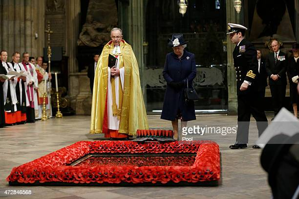 Queen Elizabeth II looks on as a wreath is laid on her behalf at the Grave of the Unknown Warrior flanked by the Dean of Westminster John Hall at the...