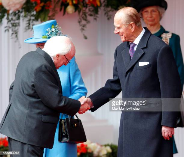 Queen Elizabeth II looks on as Irish President Michael D Higgins shakes hands with Prince Philip Duke of Edinburgh during his ceremonial welcome on...
