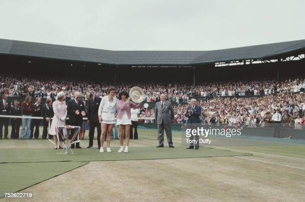 Queen Elizabeth II looks on as Virginia Wade of Great Britain holds aloft the Venus Rosewater Dish after defeating Betty Stove in their Women's...