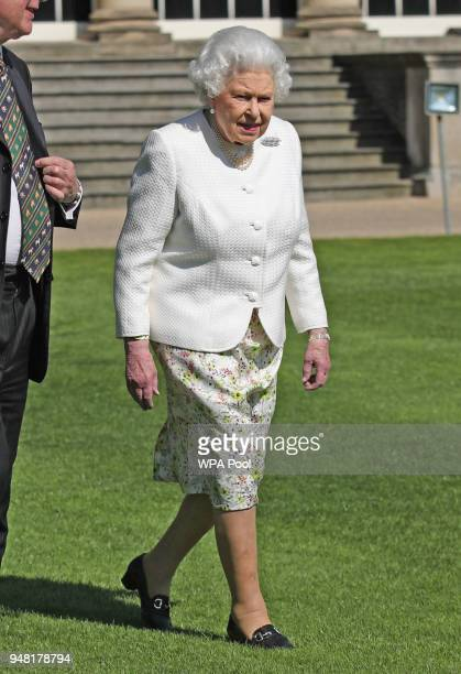 Queen Elizabeth II looks on during the unveiling of a panel marking the walkway in Buckingham Palace gardens in relation to the Commonwealth Walkway...