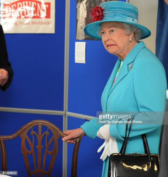 Queen Elizabeth II looks unhappy as she is reunited with a chair she sat on 30 years ago on a previous visit to Workington as she visits the...