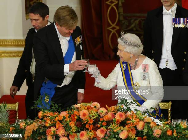 Queen Elizabeth II makes a toast alongside King Willem-Alexander of The Netherlands during a State Banquet to mark the state visit of King...