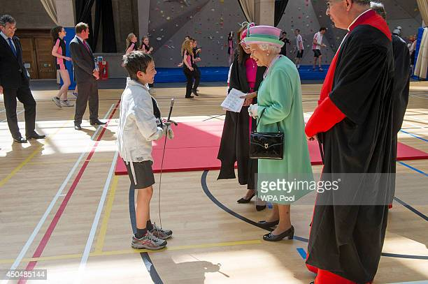 Queen Elizabeth II meets 11 year old Johan Orly who had been taking part in some fencing as she officially opens the new Westminster School's sports...