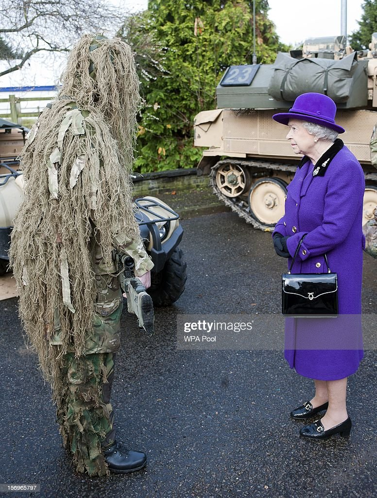 Queen Elizabeth II meets a camouflaged sniper from the Household Cavalry at Combermere Barracks on November 26, 2012 in Windsor, England.