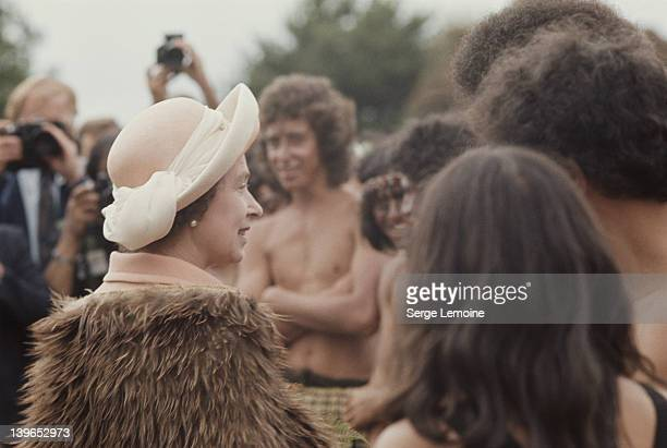 Queen Elizabeth II meets a group of Maoris during her visit to New Zealand 1977 She is wearing a traditional Maori fur cloak