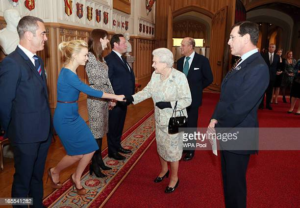 Queen Elizabeth II meets actress Carey Mulligan as actor James Nesbitt looks on at a reception for the British Film Industry at Windsor Castle on...