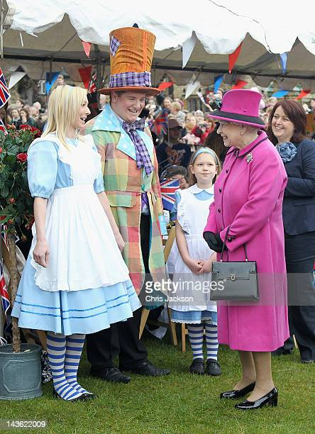 Queen Elizabeth II meets Alice and the 'Mad Hatter' as she attends a 'Mad Hatters tea party' at Sherborne Abbey on May 1 2012 in Sherborne England...