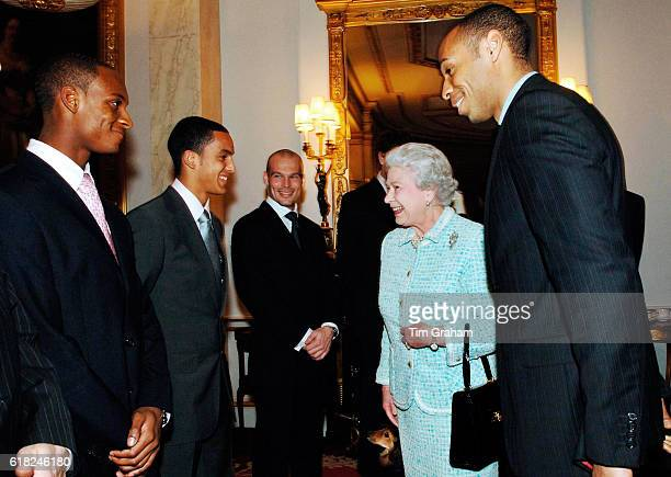 Queen Elizabeth II meets Arsenal football team members Justin Hoyte Theo Walcott Freddie Ljungberg and captain Thierry Henry at Buckingham Palace...