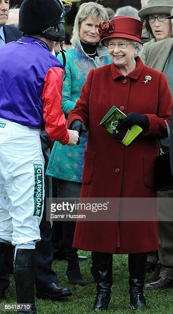 Queen Elizabeth II meets Barry Geraghty jockey of her horse Barbers Shop in the parade ring on Gold Cup day at the Cheltenham Festival on March 13...