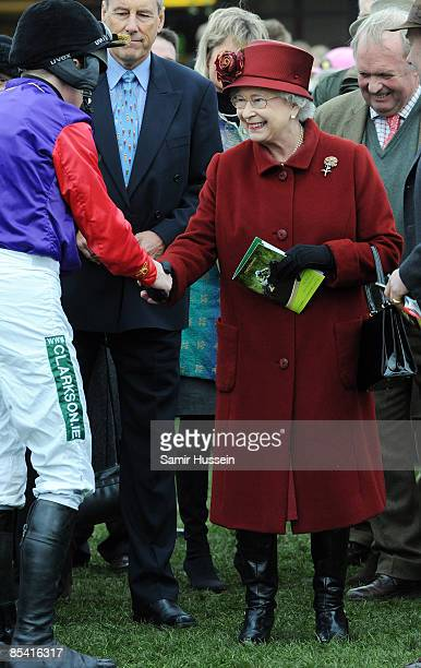 Queen Elizabeth II meets Barry Geraghty the jockey of her horse Barbers Shop in the parade ring on Gold Cup day at the Cheltenham Festival on March...