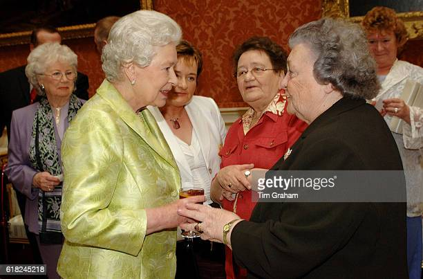 Queen Elizabeth II meets Doreen O'Leary at an 80th birthday lunch held by The Queen at home at Buckingham Palace for 99 guests who will all be...