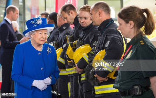 Queen Elizabeth II meets firefighters and paramedics during a visit to the Westway Sports Centre which is providing temporary shelter for those who...
