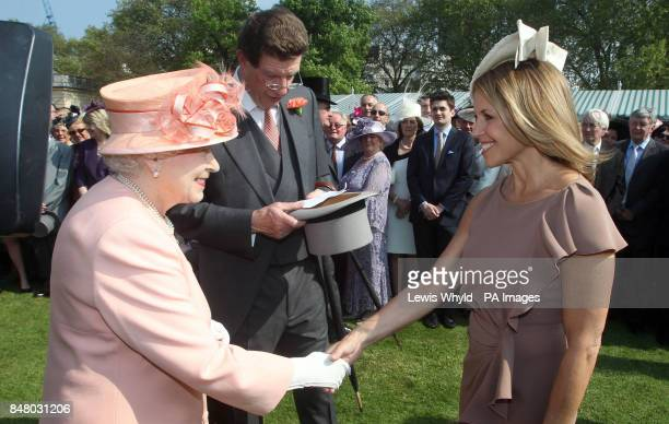 Queen Elizabeth II meets meets American television journalist Katie Couric at the first Buckingham Palace garden party of the summer London