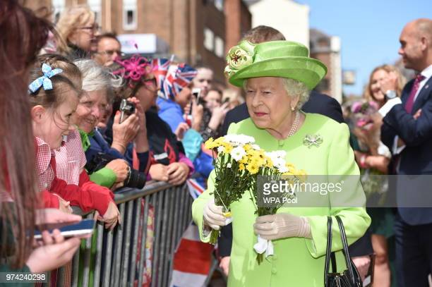 Queen Elizabeth II meets members of public as she and Meghan Duchess of Sussex walk from Storyhouse to Chester Town Hall on June 14 2018 in Chester...