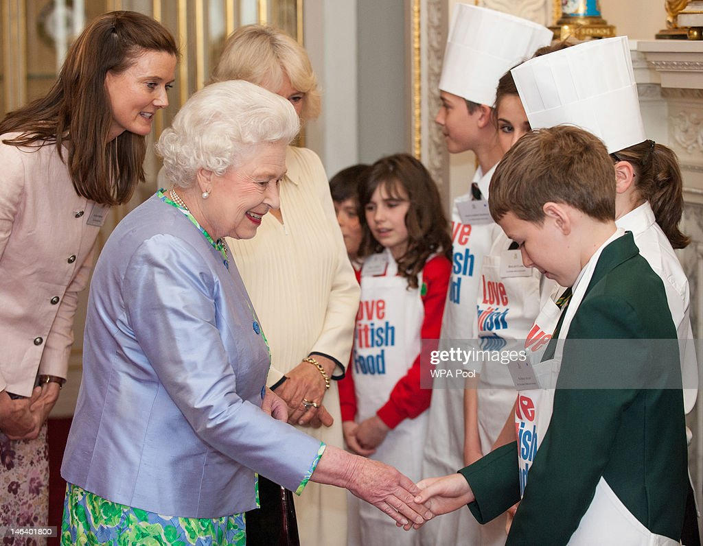 Queen Elizabeth II meets Nathan Allan, a pupil from St Columba's Primary School next to Camilla, Duchess of Cornwall during a reception at Buckingham Palace on June 15, 21012 in London, England. Queen Elizabeth II and the Duchess of Cornwall met winners of the 'Cook for the Queen' competition, who created the menu served at a reception at Buckingham Palace.