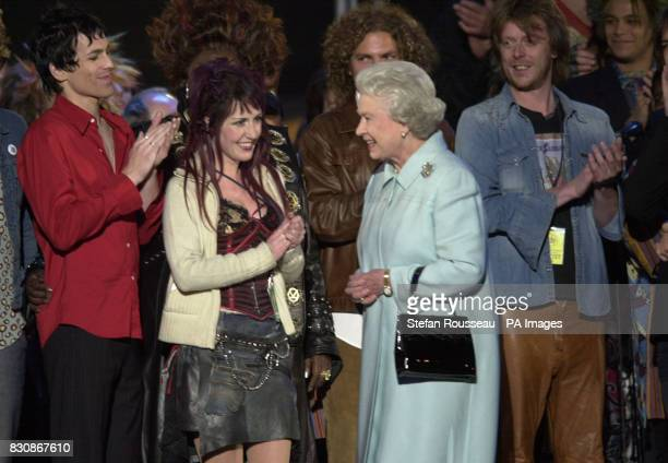 Queen Elizabeth II meets performers on stage in the gardens of Buckingham Palace after the second concert to commemorate the Golden Jubilee of...
