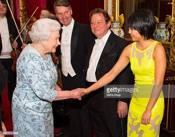 Queen Elizabeth II meets pianist Yuja Wang during a reception to mark the conclusion of the 'Moving Music' campaign and the long association of...