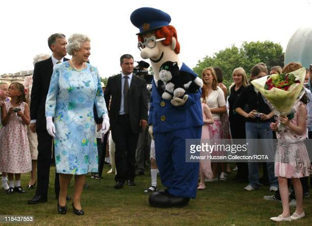 Queen Elizabeth II meets Postman Pat as she strolls through the picnic area during the Children's Garden Party