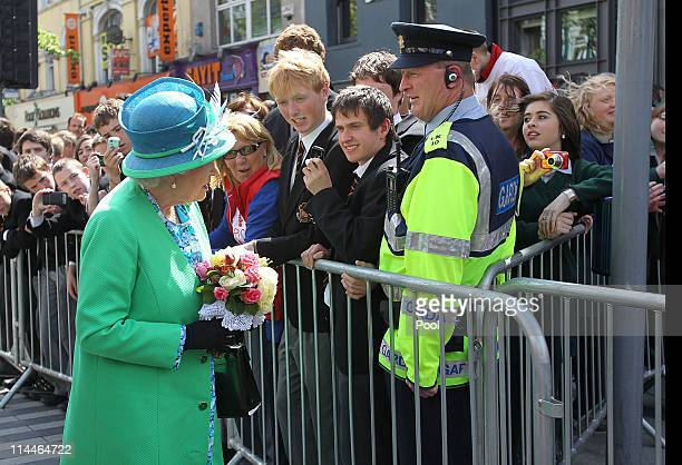 Queen Elizabeth II meets Sargeant Peter Kelly a member of the Garda Siochana outside the English Market on May 20 2011 in Cork Ireland Queen...