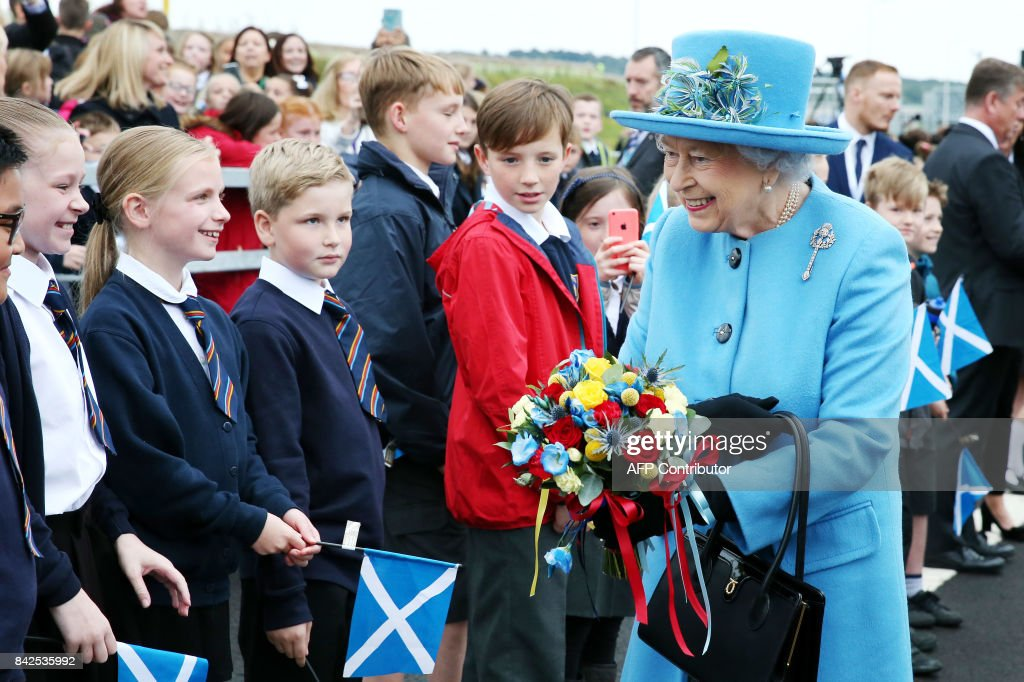 TOPSHOT - Queen Elizabeth II meets school children during the official opening ceremony for the Queensferry Crossing, a new road bridge spanning the Firth of Forth from Queensferry to North Queensferry, in Queensferry, west of Edinburgh, on September 4, 2017. The new crossing, which is the longest three-tower, cable-stayed bridge in the world, and unlike the existing bridge, is expected to remain open in all weathers. PHOTO / POOL / Andrew Milligan
