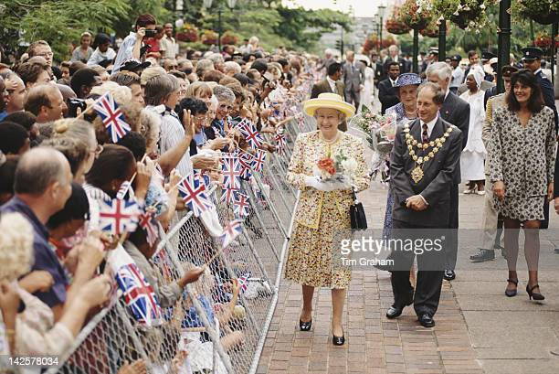 Queen Elizabeth II meets the crowds in front of the town hall during a visit to Durban South Africa 25th March 1995 She is accompanied by Mike...