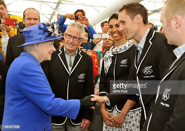 Queen Elizabeth II meets the Nick Willis of New Zealand as she and the Duke of Edinburgh tour the Athletes Village dinning hall during a tour of the...