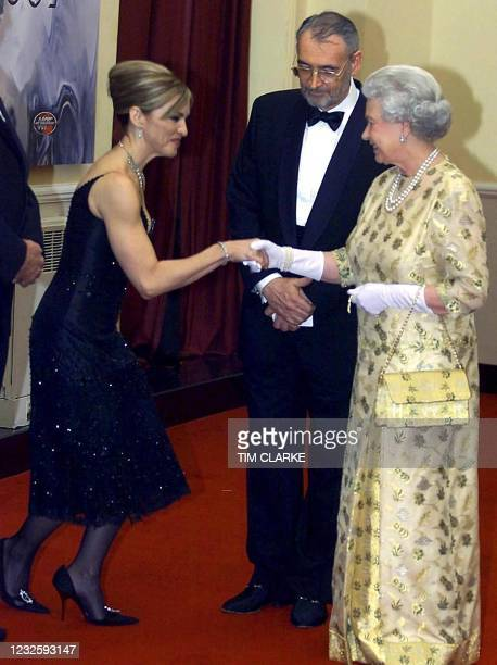 """Queen Elizabeth II meets US pop star and actress Madonna watched by producer Michael Wilson at the World premiere of the latest Bond movie """"Die..."""