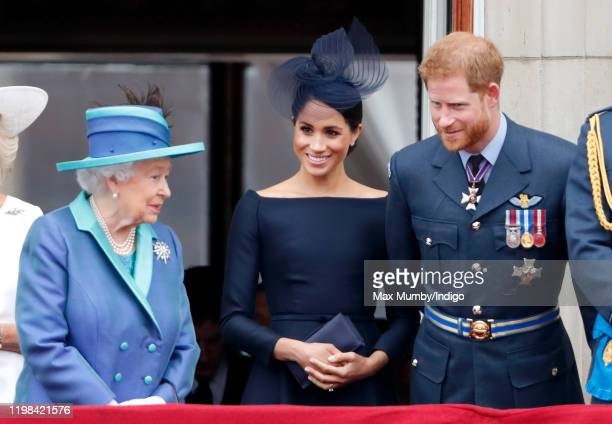 Queen Elizabeth II Meghan Duchess of Sussex and Prince Harry Duke of Sussex watch a flypast to mark the centenary of the Royal Air Force from the...