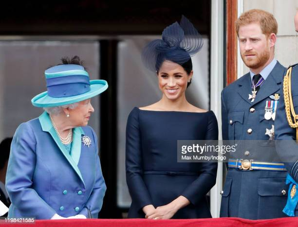 Queen Elizabeth II, Meghan, Duchess of Sussex and Prince Harry, Duke of Sussex watch a flypast to mark the centenary of the Royal Air Force from the...
