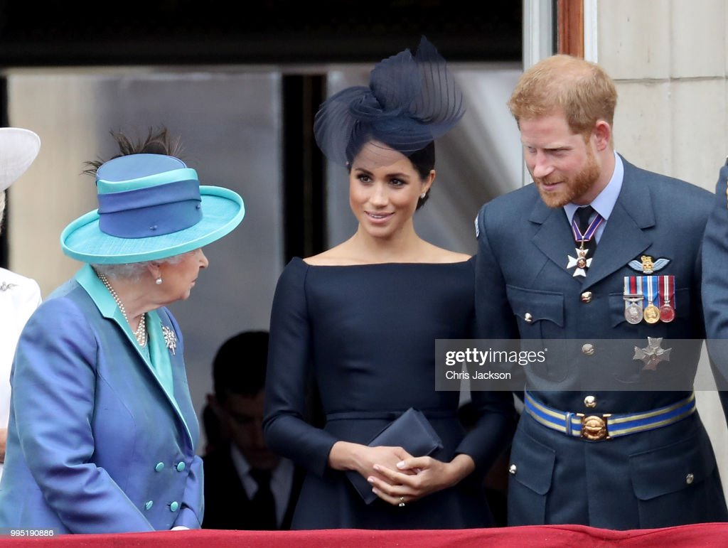 Queen Elizabeth II, Meghan, Duchess of Sussex and Prince Harry, Duke of Sussex watch the RAF flypast on the balcony of Buckingham Palace, as members of the Royal Family attend events to mark the centenary of the RAF on July 10, 2018 in London, England.