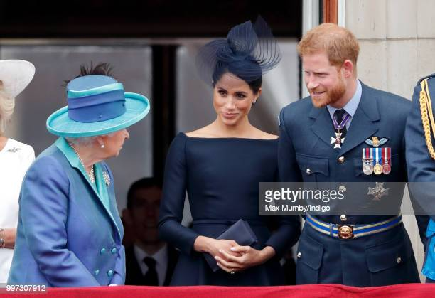 Queen Elizabeth II, Meghan, Duchess of Sussex and Prince Harry, Duke of Sussex, watch a flypast to mark the centenary of the Royal Air Force from the...