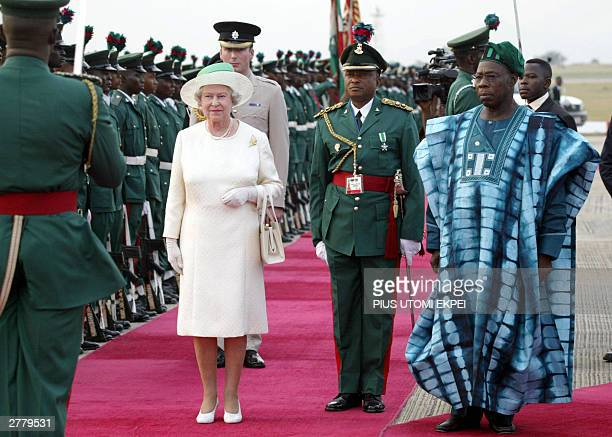 Queen Elizabeth II of England and Nigerian President Olusegun Obasanjo review the honor guard upon her arrival at Nnamdi Azikiwe International...